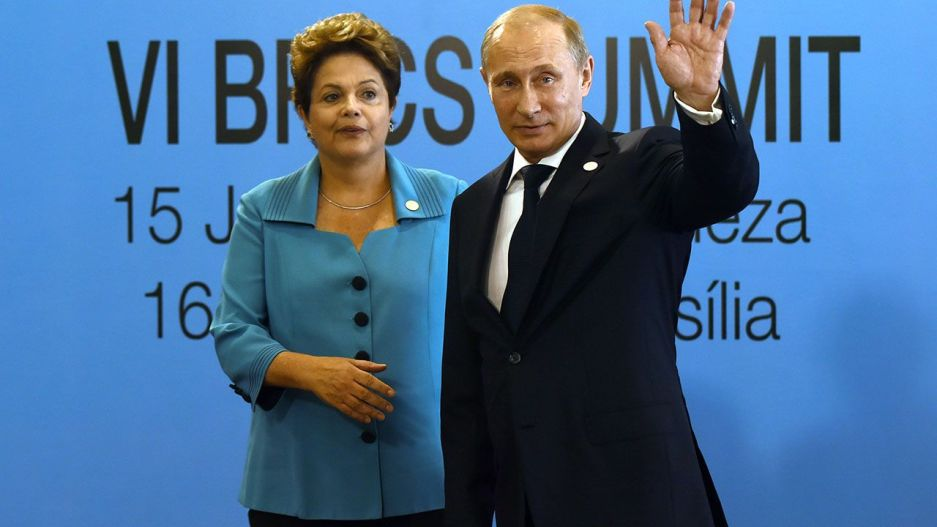 Brazilian President Dilma Rousseff (L) welcomes Russian President Vladimir Putin upon his arrival to the 6th BRICS summit in Fortaleza, Brazil, on July 15, 2014.  Leaders of the BRICS (Brazil, Russia, India, China and South Africa) group of emerging powers gathered in Brazil on Tuesday to launch a new development bank and a reserve fund seen as counterweights to Western-led financial institutions. AFP PHOTO / YASUYOSHI CHIBA